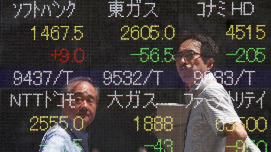 Two men are shown in a reflection of a stock market ticker wearing collared shirts