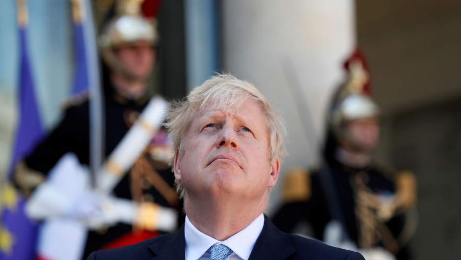 British Prime Minister Boris Johnson is shown looking up and wearing a suit and blue tie with Élysée Palace guards in soft focus in the background.