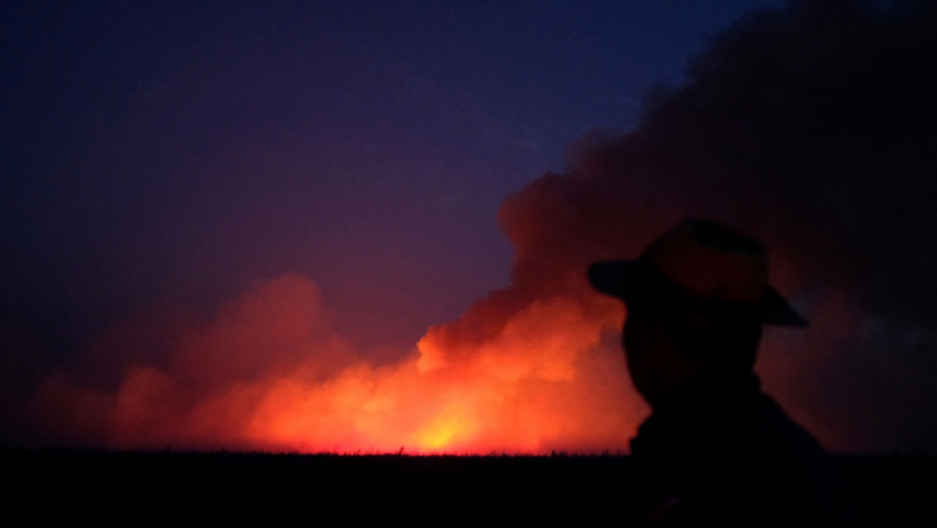 A man wearing a have is shown in the near ground, black in shadow, with a brigh orange fire seen in the distance.
