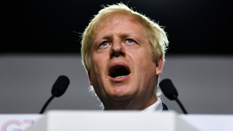 Britain's Prime Minister Boris Johnson is shown standing behind two small microphones with his mouth open speaking.