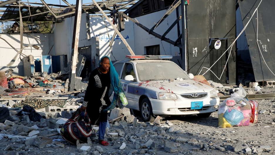 A woman carries belongings outside of a detention center in rubble