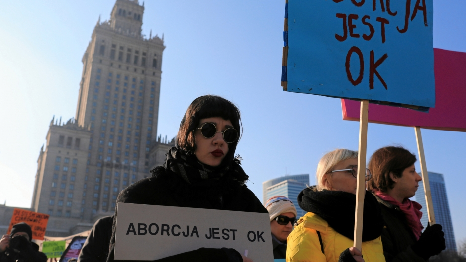 "woman wearing sunglasses holds sign that says ""abortion is ok"""
