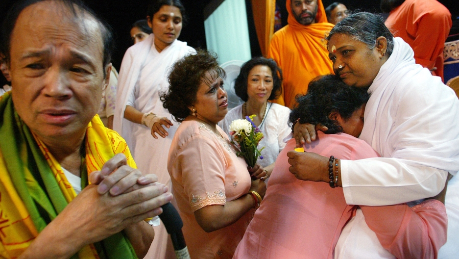 Amma embraces a devotee surrounded by others in orange and white robes