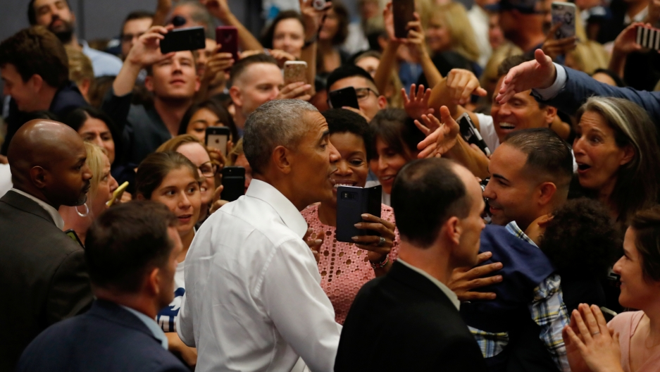 A large group of people surround former President Barack Obama