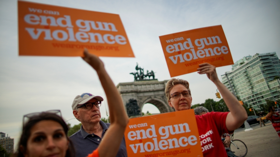 "Protesters hold signs that say ""We can end gun violence."""