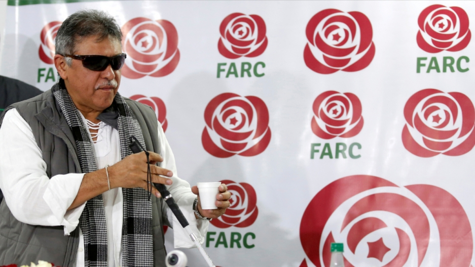 A man walks in front of a banner with the words FARC