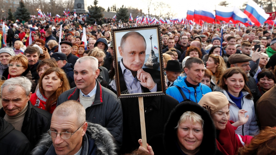 A crowd of people wave Russian flags and one holds up a photo of Putin on a sign