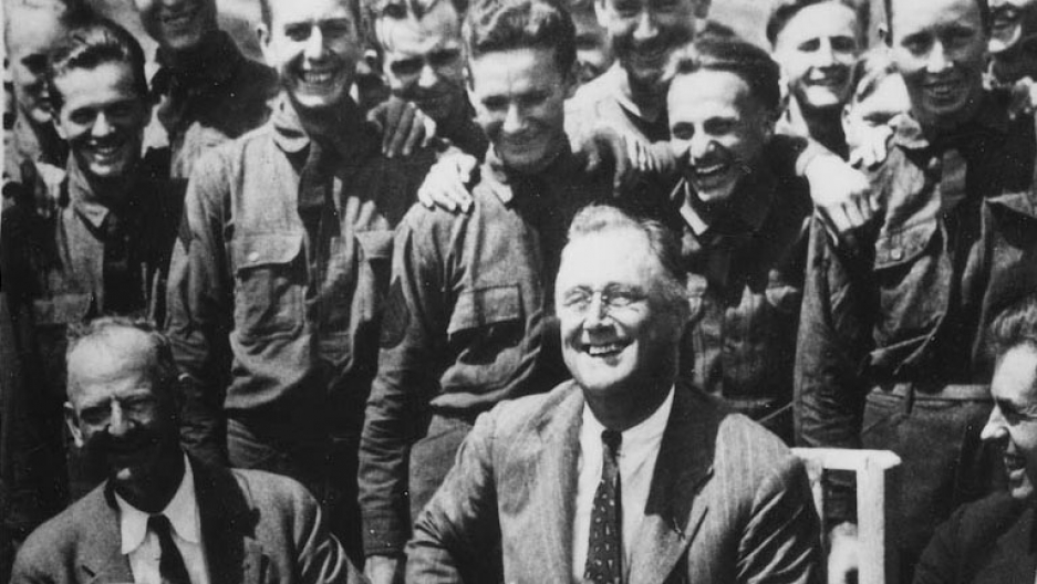 President Franklin Roosevelt poses for a photo with other men behind him in a historical image