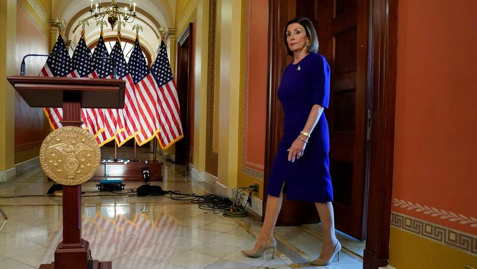 Nancy Pelosi walks up to a podium with a line of American flags set up behind it