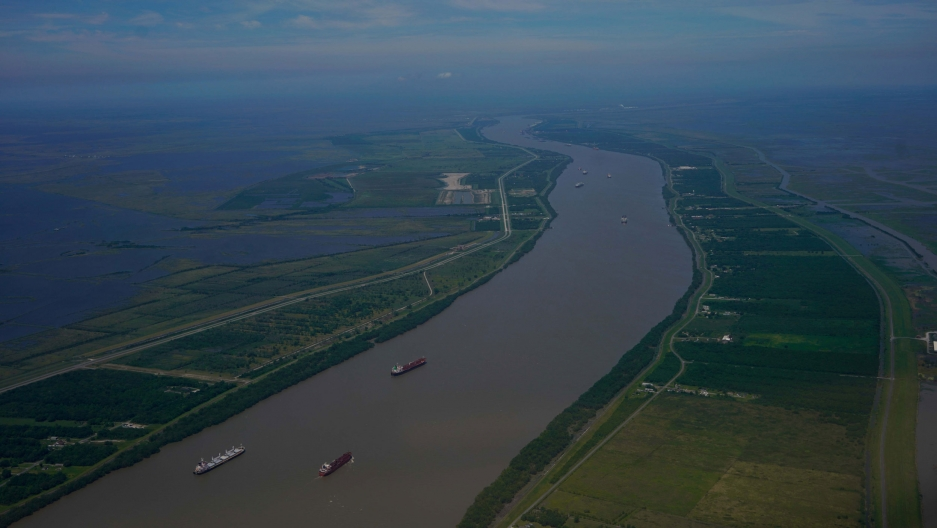 The Mississippi River as seen from flying above in an airplane shows several boats carrying goods.