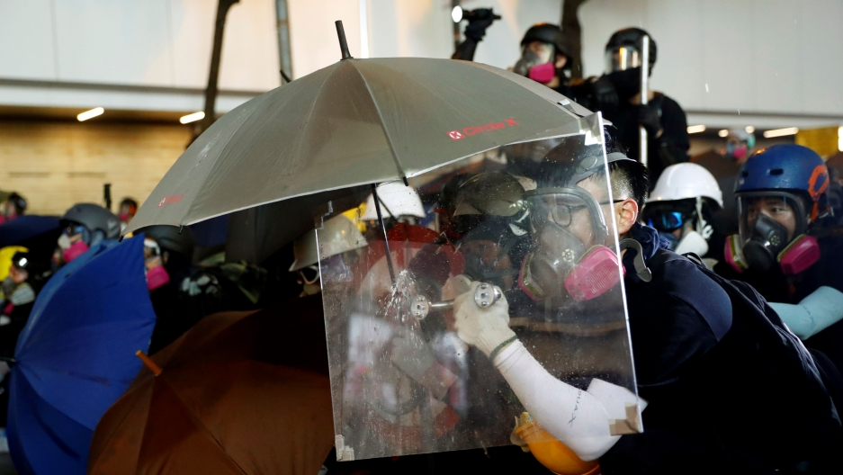 A demonstrator uses a makeshift shield to take cover during a protest in Hong Kong