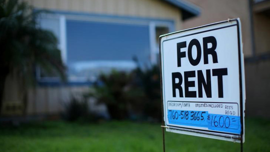 "A ""For Rent"" sign in focus in font of a house."