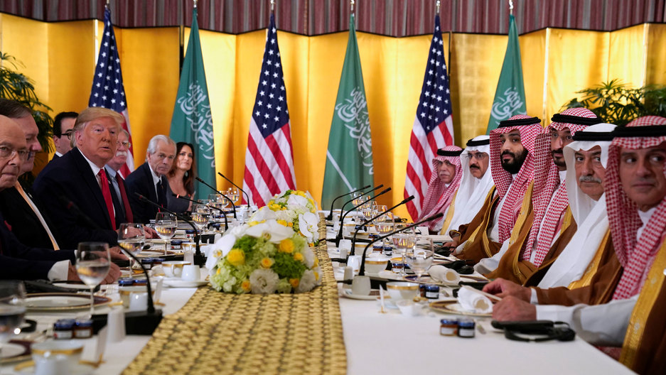 A long table is shown from one end with President Trump's dark-suit-clad team sits across from Saudi Arabia's Crown Prince Mohammed bin Salman's team wearing traditional checkered head dresses.
