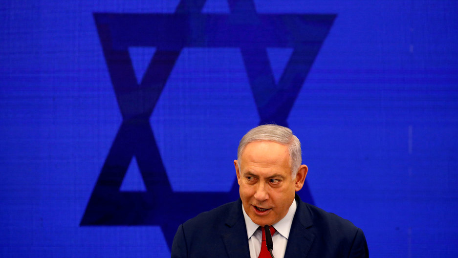 Israeli Prime Minister Benjamin Netanyahu is shown wearing a dark suit and red tie with the Star of David behind him.