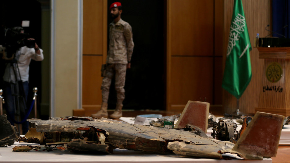 A pile of metal wreckage is shown on a table in the nearground with an armed security personel in the background.