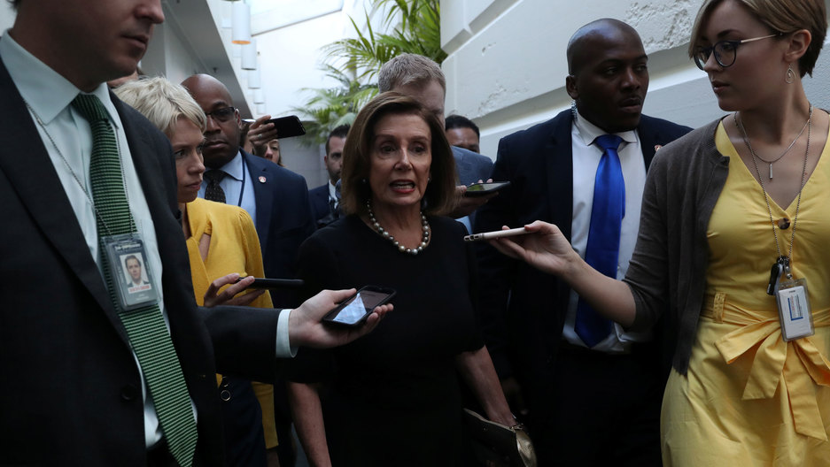 US House Speaker Nancy Pelosi is shown wearing a dark dress and pearls while surrounded by reporters.