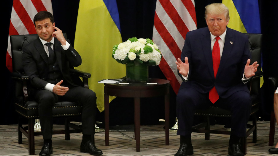 Ukraine's President Volodymyr Zelenskiy is shown seated next to US President Donald Trump with their respective flags placed behind them.