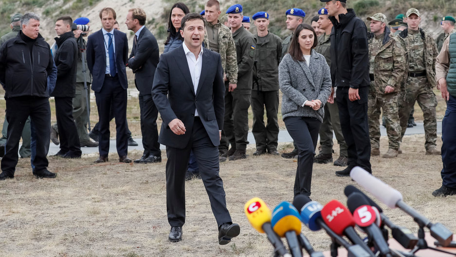 Ukrainian President Zelenskiy is shown wearing a dark suite and walking toward several microphones in an outdoors setting.
