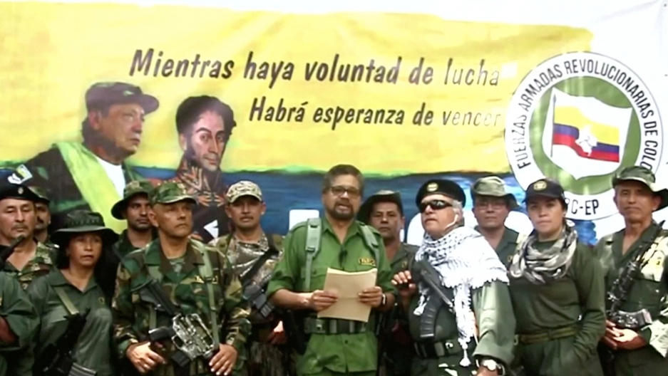 A group of FARC soldiers stand together reading from a paper.