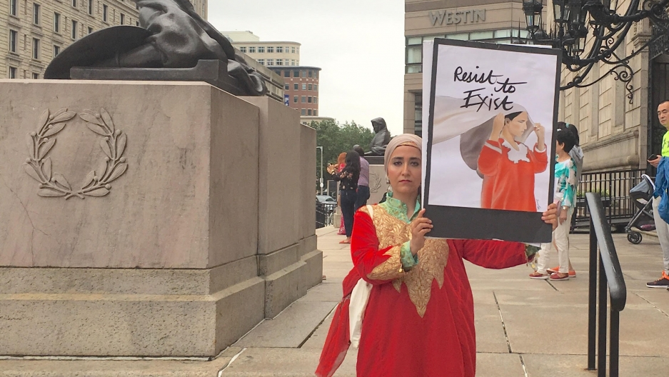 A woman in a red pheran stands holding an image of a woman in a red pheran