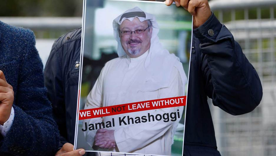 "A man holds a sign that says ""we will not leave without Jamal Khashoggi"""