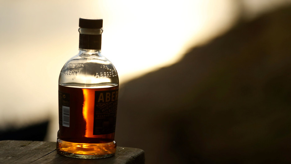 A bottle of whisky is left on a bank.