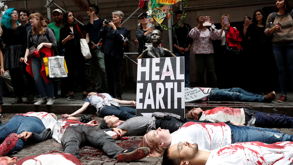 Climate change activists protest at the Wall Street Bull in Lower Manhattan during Extinction Rebellion protests in New York City, New York, US, on Oct. 7, 2019.