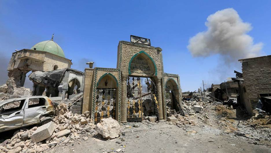 The front of mosque is seen amid rubble. Behind the door, is a distinctive blue dome.