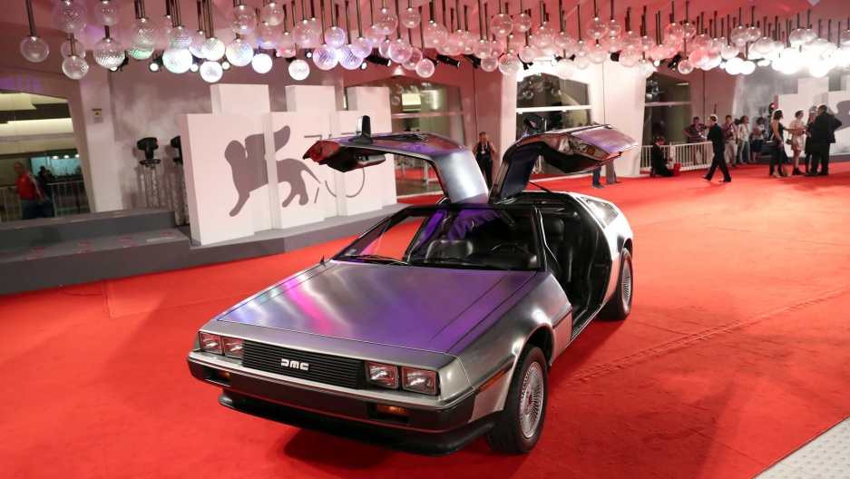 A Delorean car sits with it's iconic doors open on a red carpet