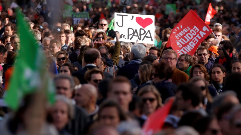 "A crowd of people carry flags. One holds a sign that says ""J'[HEART] Papa."