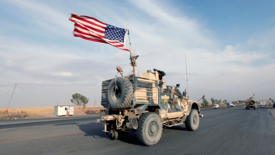 A military truck drives down a road with an American flag blowing in the wind on top of the truck
