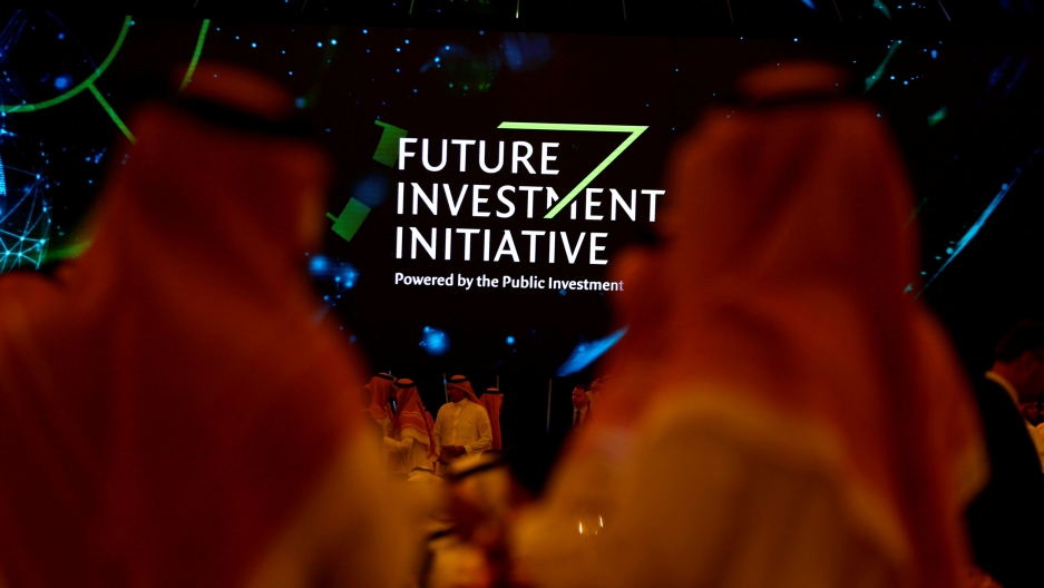 "A sign reading ""Future Investment Initiative"" is visible between the heads of two men"