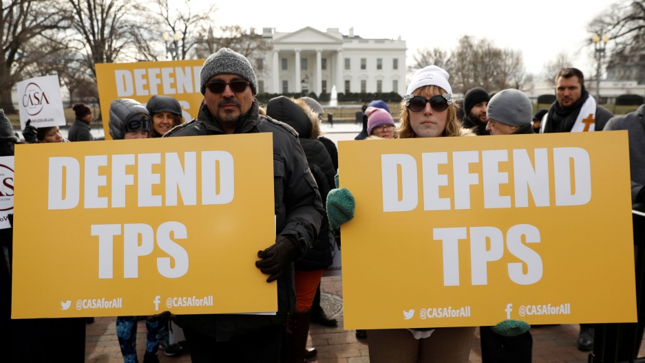 "People hold bright yellow signs reading ""Defend TPS"" in front of the White House in Washington, DC."