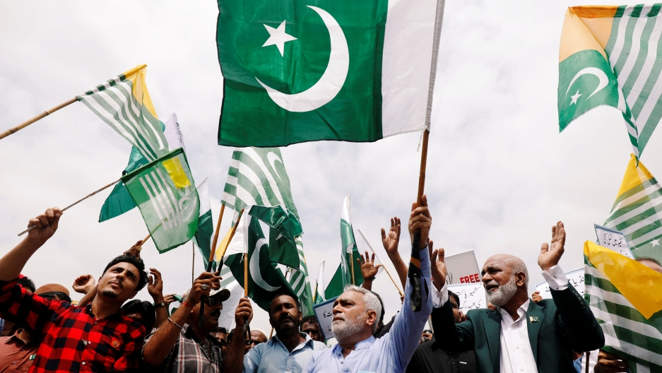 People carry Pakistan's and Azad Kashmir's green flags and chant slogans to express solidarity with the people of Kashmir, in Karachi, Pakistan, August 30, 2019.