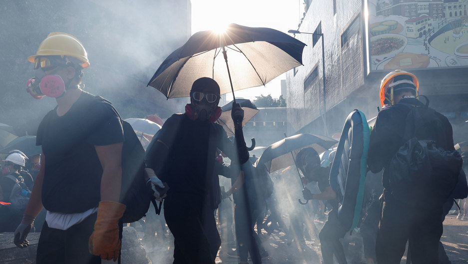 Several people are shown shrowded in smoke with one person holding a dark umbrella up to refract the sunlight.