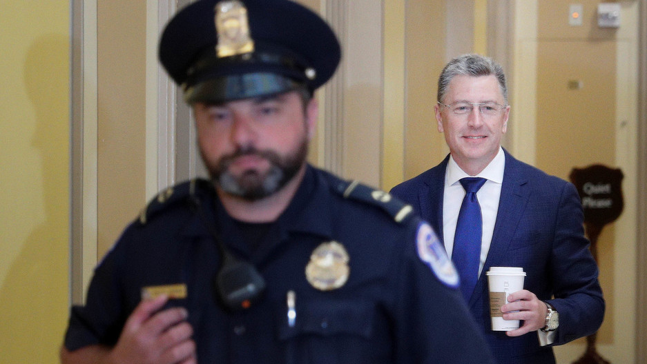 A uniformed officer walks in front of a man in a suit smiling and holding a coffee