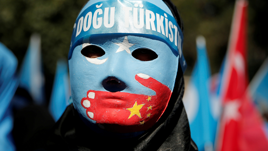 A demonstrator wears a blue mask with a red hand painted across the mouth area.