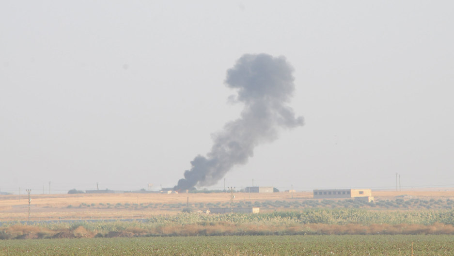 Smoke rises from a structure shown off in the distance.