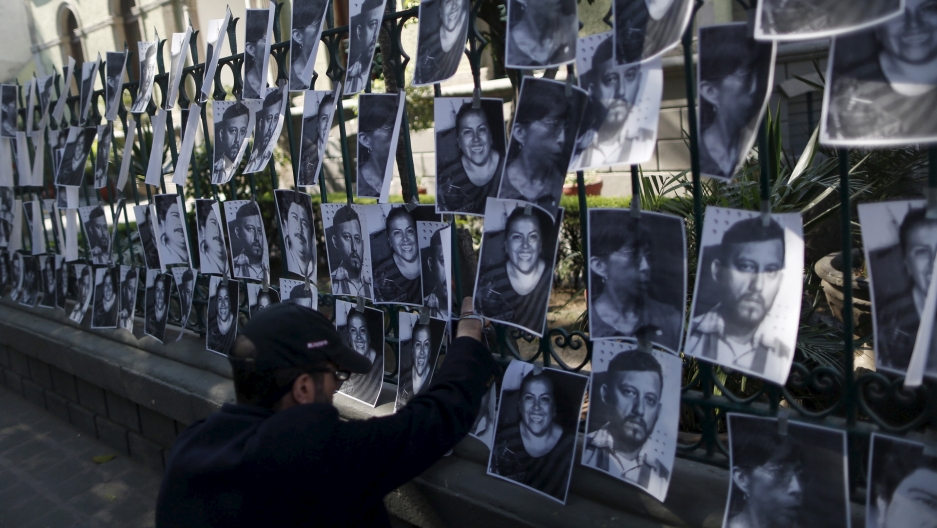 A man hangs images of murdered journalists during a demonstration against the murder of a journalist Anabel Flores outside the Government of Veracruz building in Mexico City, February 11, 2016.