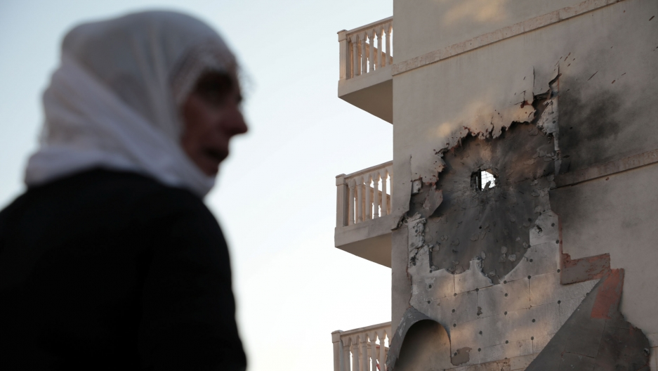 A woman is shown in soft focus in the nearground with an apartment building in the background that has bombed.