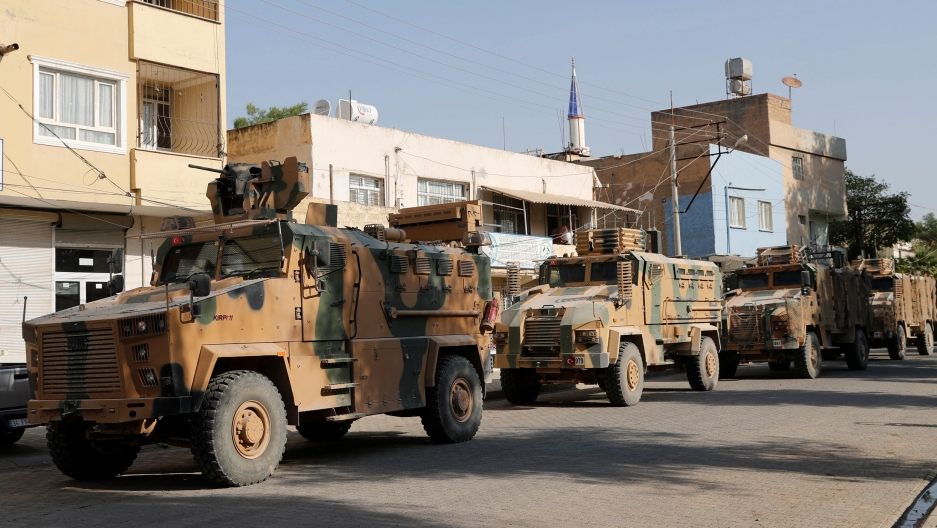 A line of Turkish military vehicles are shown driving in an abandoned street.