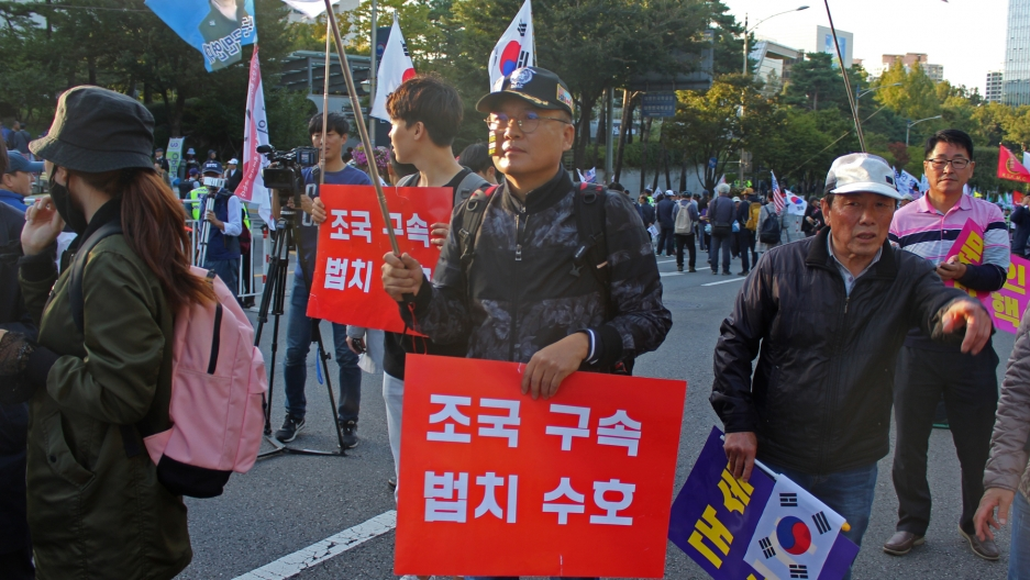 Man stands at protest with red sign and white letters in Korean