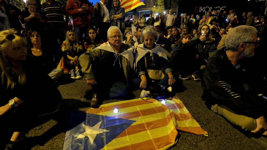 A group of people gather around a flag in a night-time protest with low lights