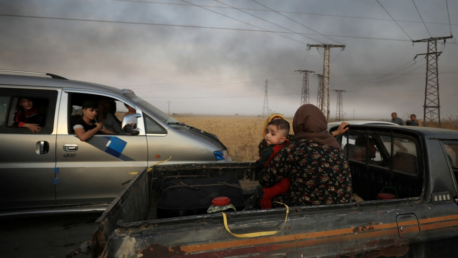 A woman with a baby sits at the back of a truck as they flee Ras al-Ain town, Syria, on Oct. 9, 2019.