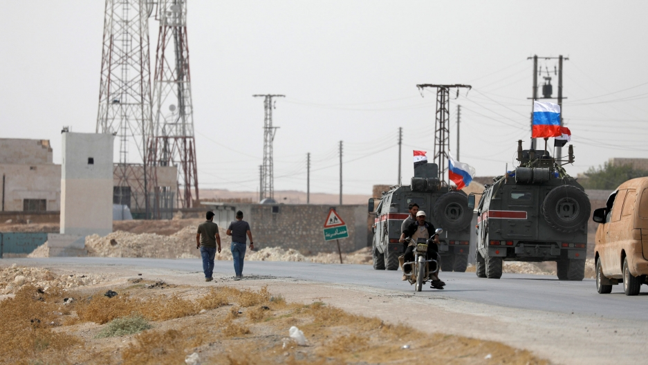Two military trucks are show driving with Russian and Syrian flags flying on top.