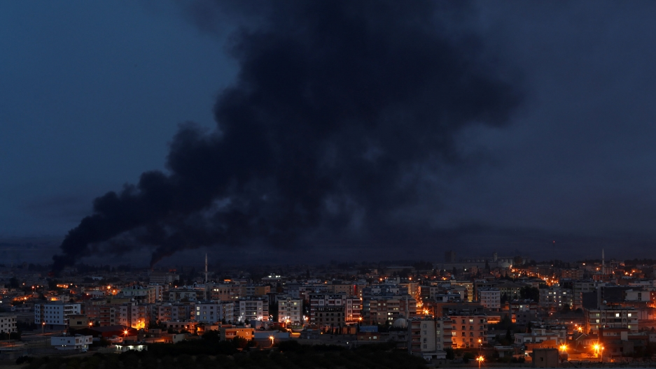 Black smoke is show rises from the Syrian town of Ras al Ain as night falls and streetlights glow.