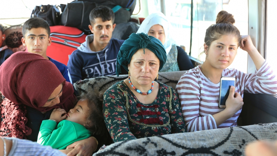Syrian displaced families who fled violence after the Turkish offensive against Syria, sit in a bus on their way to camps on the outskirts of Dohuk, Iraq, on October 16, 2019.