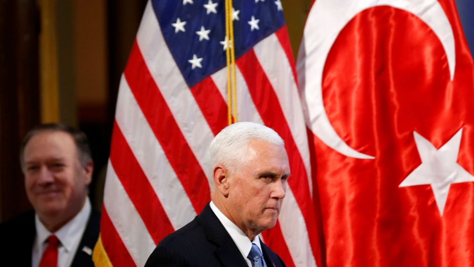 US Vice President Mike Pence is shown wearing a dark suit and blue tie and walking past the US and Turkey flags