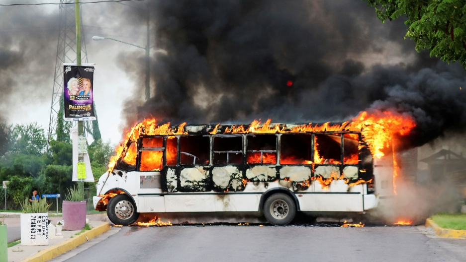 A white bus is shown ablaze and blocking a road with black smoke coming from it.