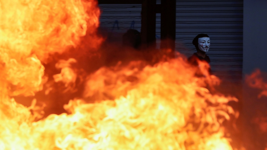 A demonstrator wearing a Guy Fawkes mask is shown walking past a large fire.